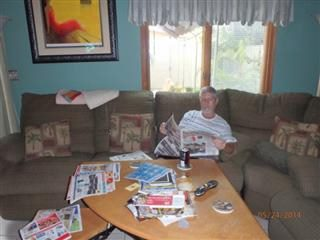 A man sitting on a couch reading a newspaper with other newspaper sections strewn across a coffee table.