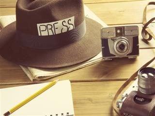 """Chapeau avec l'étiquette """"presse"""" Il y avait un cahier avec un crayon et deux appareils photo étalés sur une table."""