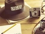 "hat with the label ""press"" on it, a notebook with a pencil on it and two cameras spread across a table."