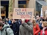 "people at a rally holding a sign reading ""do we look like bots?"""