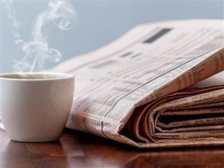 Journal à côté d'une tasse de café sur une table.