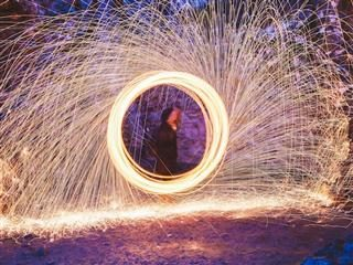sparks shooting off of a circle, view of a person walking through the center