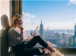 Thoughtful female sitting by a window with a city view, while researching a potential product purchase on her tablet - multitouch-attribution-customer journey concept