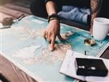 A person planning a trip with a map on a table