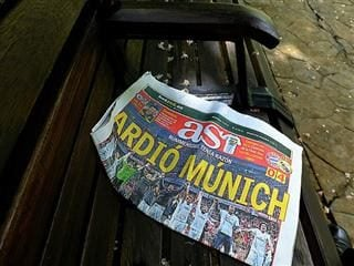 "Newspaper on a bench. Headline says, ""Ardio Munich."""