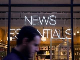 "man walking in front of a ""news essentials"" store with neon sign"
