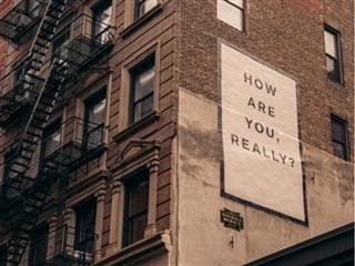 how are you message billboard on the side of a city apartment building