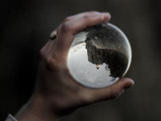 hand holding crystal ball with person visible inside