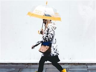 woman walking up the street under a see-through umbrella