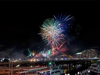Image of a harbor at nighttime with colorful fireworks going off ahead.