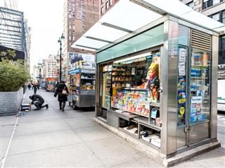 An April, 2018 scene from midtown Manhattan: a street sidewalk on Broadway with a newsstand with newspapers, magazines and candy.