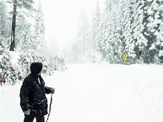 man walking through snowy woods looking back over his shoulder