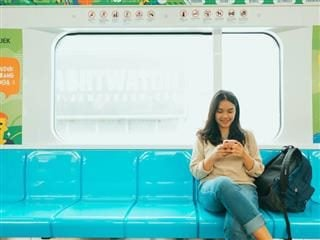 woman looking down at her phone while riding an empty subway