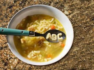 A bowl of chicken soup with a spoonful spelling ABC