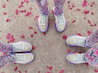 view from above of three people's legs in matching pants and sneakers with flowers on the ground
