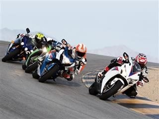 four motorcyclists racing around a curve