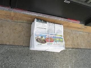 Stack of newspapers in a bundle on the ground.