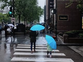 mother and daughter walking up the street  with matching umbrellas
