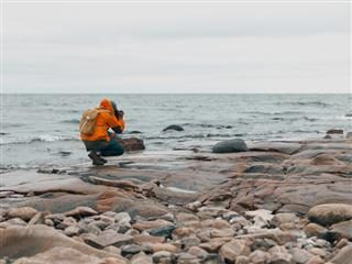 person on a rocky beach in Sweden taking a photo of the horizon