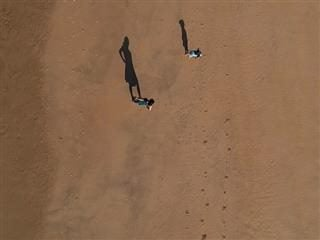 two people on the beach from above with  visible footprints  in the sand