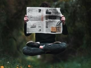 A man in lotus position levitating while reading the newspaper - Workplace Newsbyte