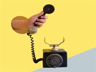surreal image of arm coming out of yellow wall holding the receiver of an old phone