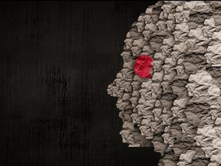 Hundreds of different colored skulls made of paper collaged together on a black background - Multicultural Marketing concept