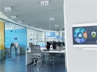 An empty workplace office with a monitor on the wall with an automated security system