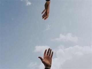 hands reaching for each other, sky in between