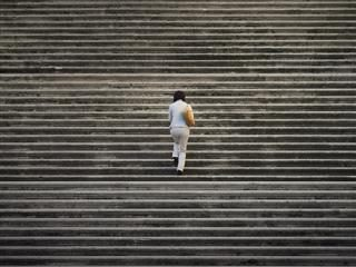 woman walking up a long flight of stairs