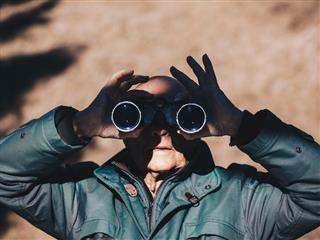 man facing camera with binoculars over his eyes