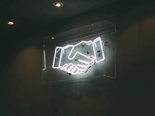 a neon sign showing a handshake