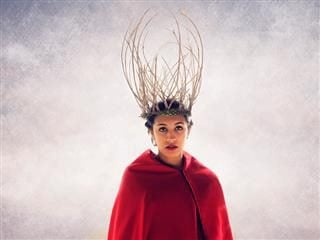 Woman in a red cape with a crown of deer antlers on her head.