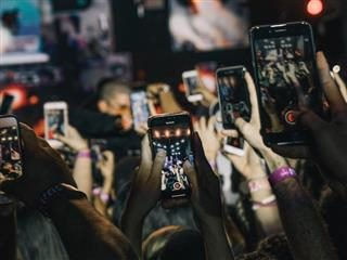audience at a concert, all holding up their smartphones