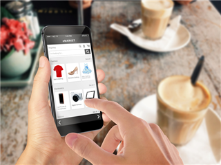 A man sitting at a restaurant table, while shopping on his smartphone - Mobile commerce concept