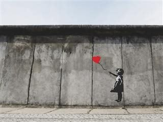 graffiti paste up of a girl letting go of a heart shaped balloon