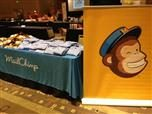 A table with a Mailchimp tablecloth and Mailchimp-theme shirts on top, next to a post with the Mailchimp logo on it.