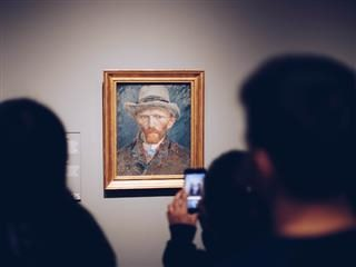 Vincent Van Gogh painting hanging in a museum with a viewer taking a digital photo of it