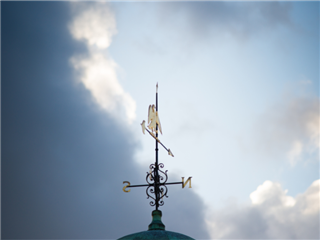 A weather vane pointing to true north under a sky with dark clouds forming