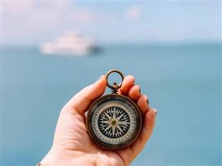 hand holding a compass against a backdrop of an ocean and a liner