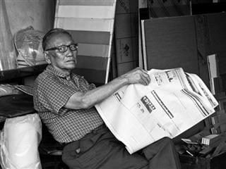 Man sitting down looking at the camera as he turns the page in a newspaper.