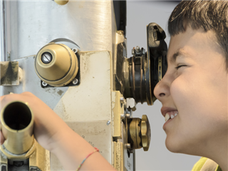 A child peers through a submarine periscope