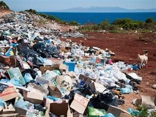 garbage dump in foreground, beautiful sea and mountains in background