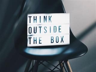 think outside the box sign resting on an Eames chair