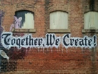 "graffiti which reads ""Together, we create!"" on a brick building"