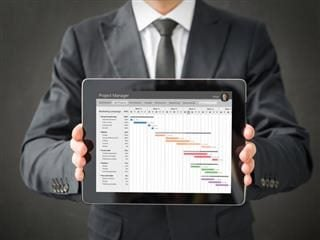 A businessman holding a tablet in both hands presenting a piece of project management software