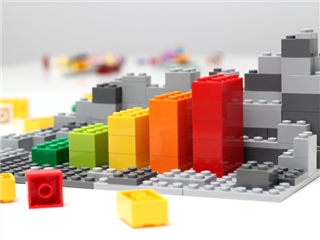 Progress chart made of Lego-like bricks. Isometric composition of colorful toys on white table - building concept