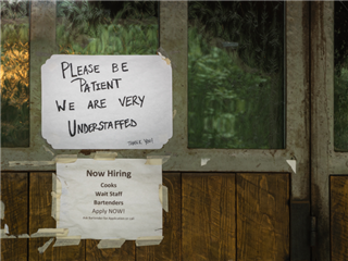 Sign in restaurant window during time of COVID-19 stating restaurant is understaffed and is hiring.