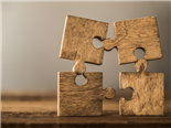 Wooden puzzles pieces leaning on one another