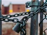 a close up of a chain and lock securing a gate